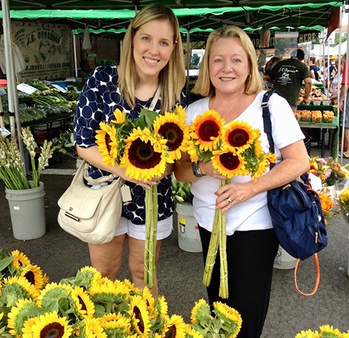Two women holding sunflowers at the farmers market